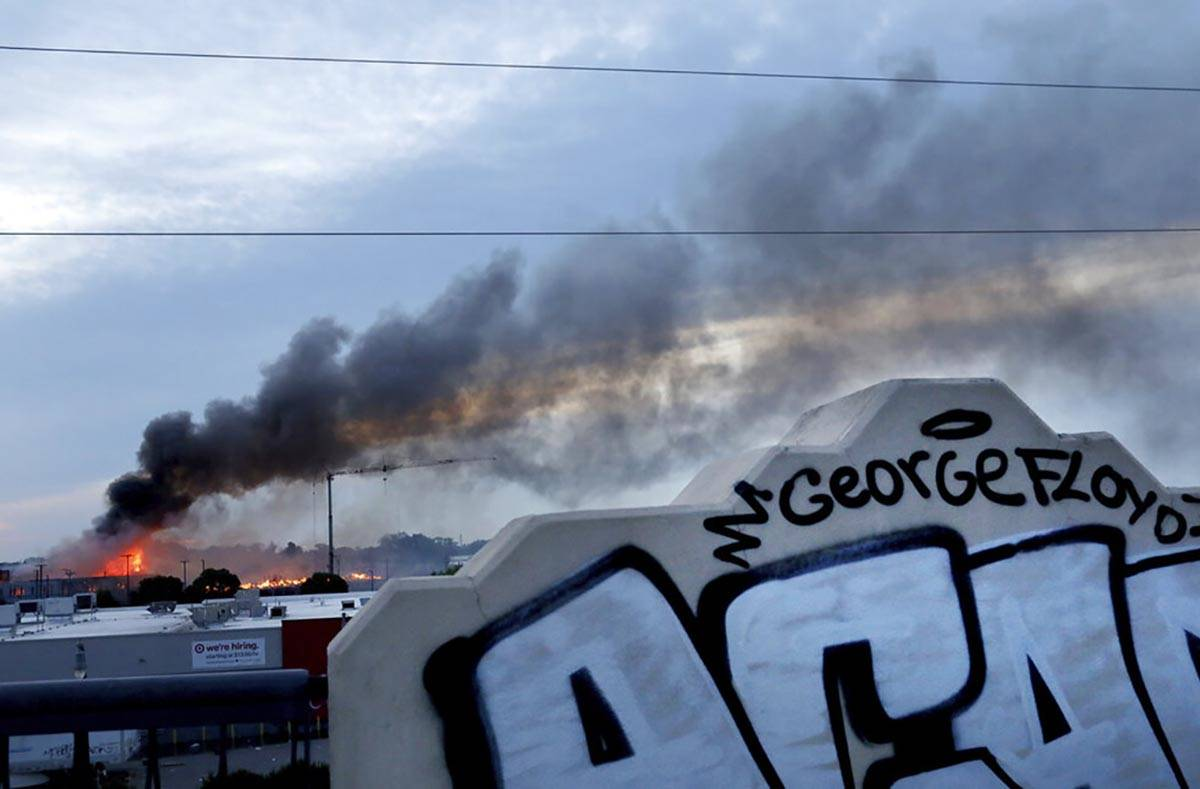 Smoke fills the sky after a night of unrest and protests in the death of George Floyd early Thu ...