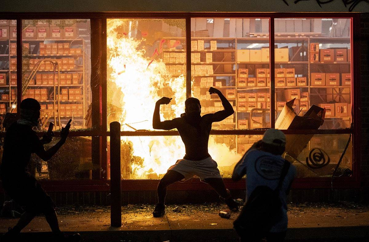 A man poses for photos in front of a fire at an AutoZone store, while protesters hold a rally f ...
