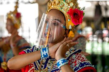 A Thai classical dancer wearing face shield to help curb the spread of the coronavirus performs ...