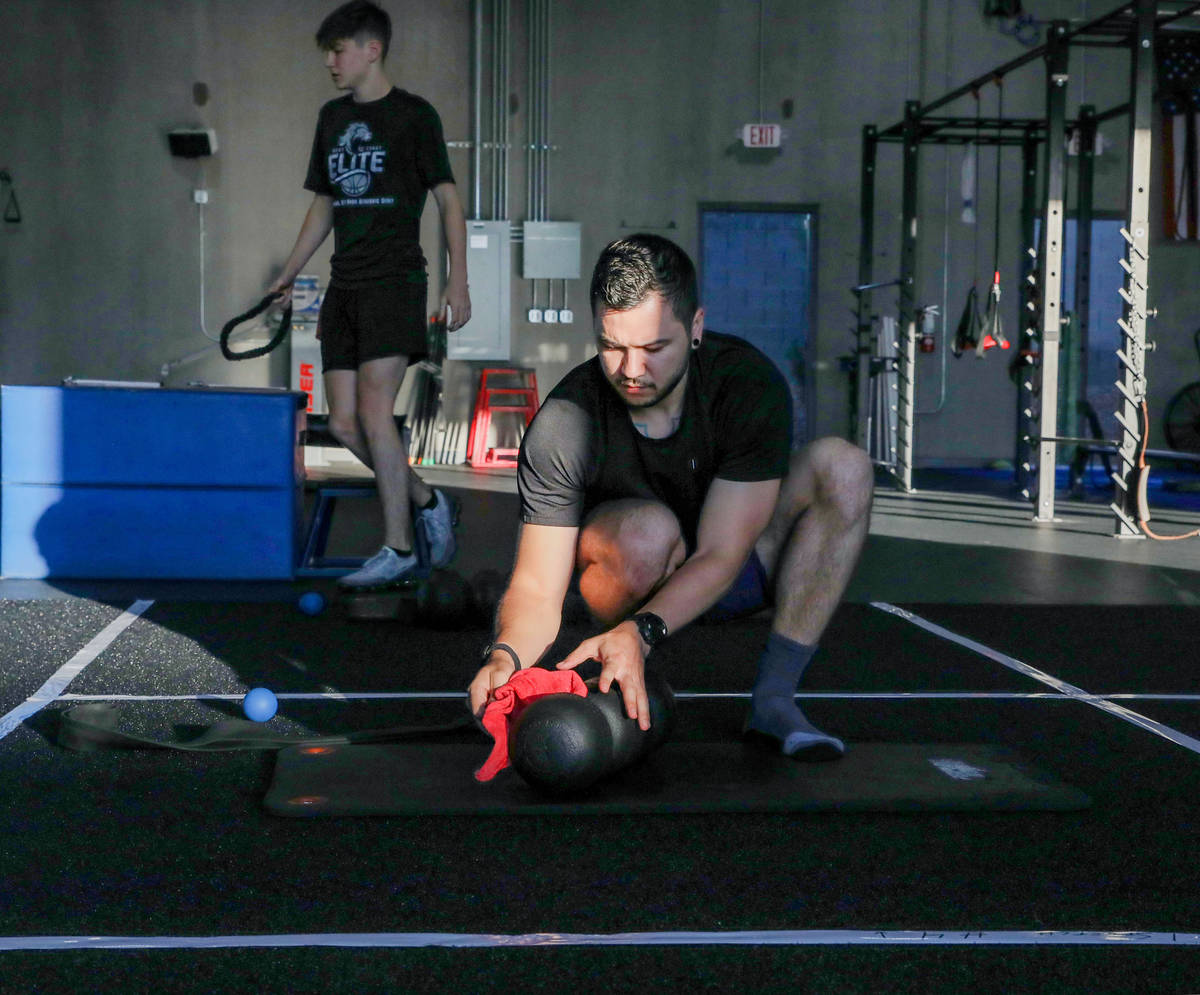Brian Lee, member of The Gym Las Vegas, disinfects his mat, the first morning on the facility's ...