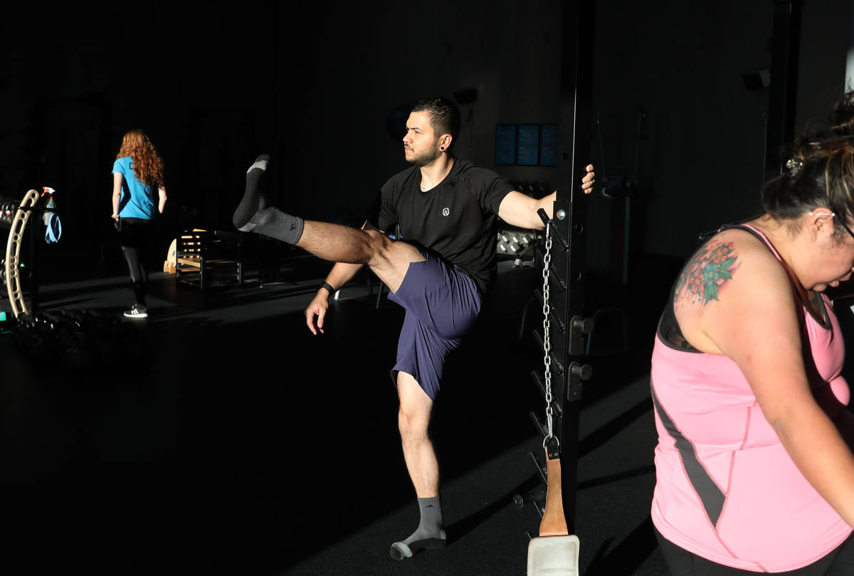 Brian Lee, member of The Gym Las Vegas, partakes in strength training while following social di ...