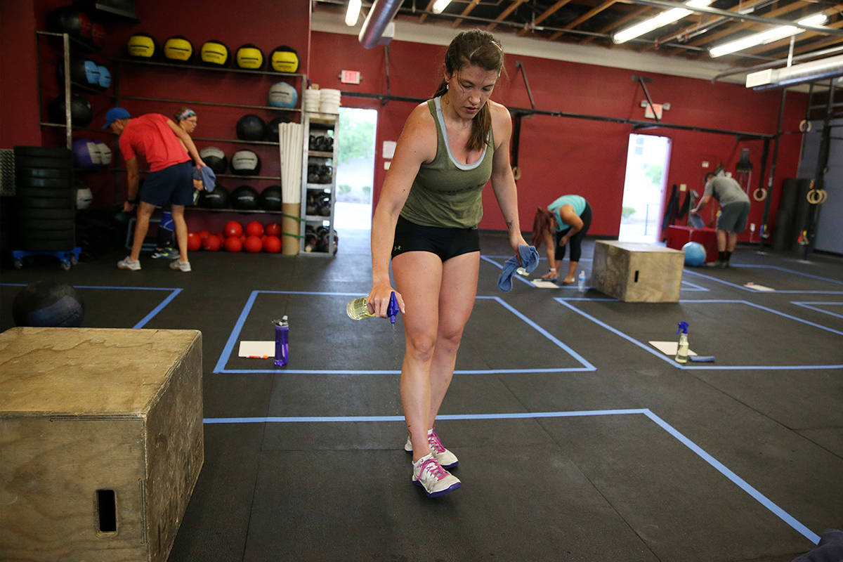 Kaydee Weida cleans her space after working out during a class at Crossfit Apollo in Las Vegas, ...