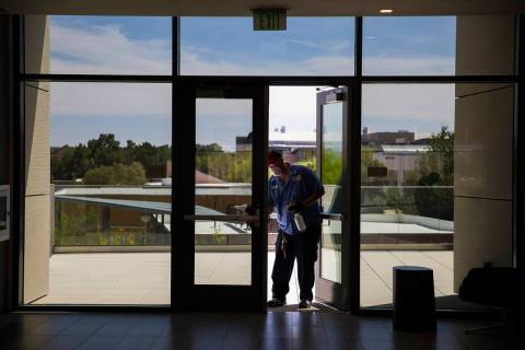 Robert Lucas, left, a custodian supervisor, sanitizes a door in the Hospitality Hall at UNLV in ...