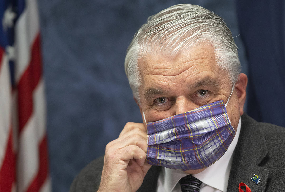 Gov. Steve Sisolak wears a protective mask before the start of a press conference, April 8, 202 ...