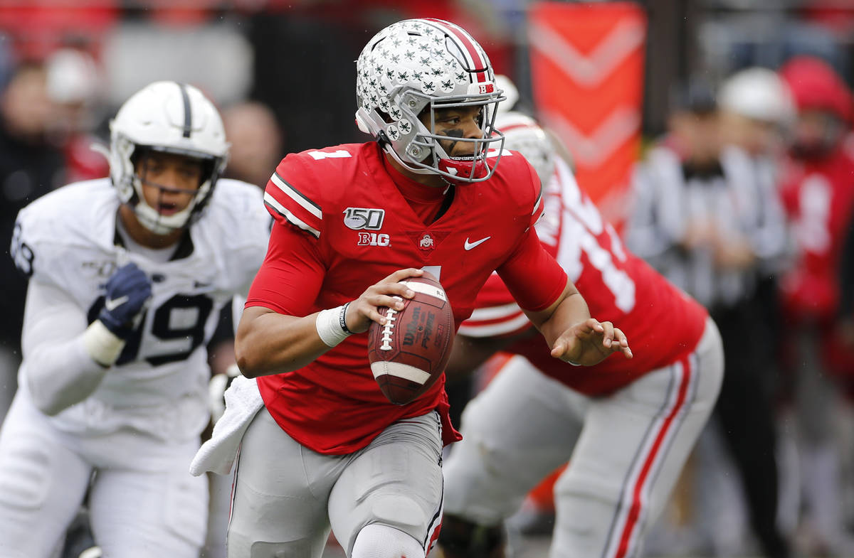Ohio State quarterback Justin Fields, right, looks for an open receiver as Penn State defensive ...