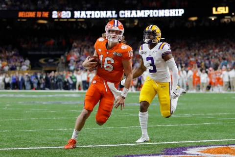 Clemson quarterback Trevor Lawrence scores past LSU safety JaCoby Stevens during the first half ...