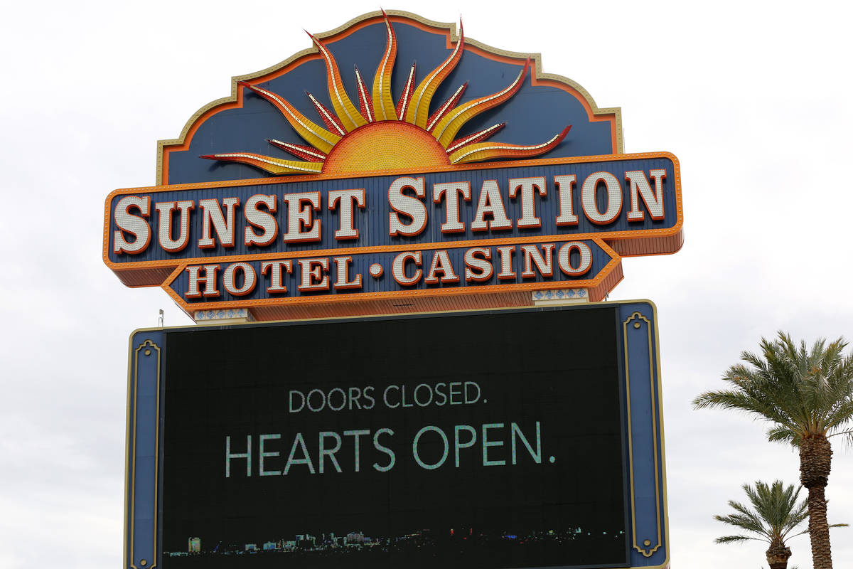 Sunset Station sign towers over an empty, blocked off parking lot after casinos were ordered cl ...