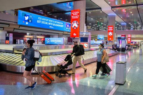 Travelers walk by new signage outlining coronavirus safety guidelines in the baggage claim area ...