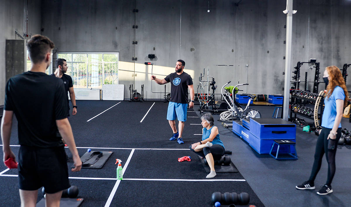 Owner of The Gym Las Vegas Rob Martinez, center, gives strict social distancing instructions to ...