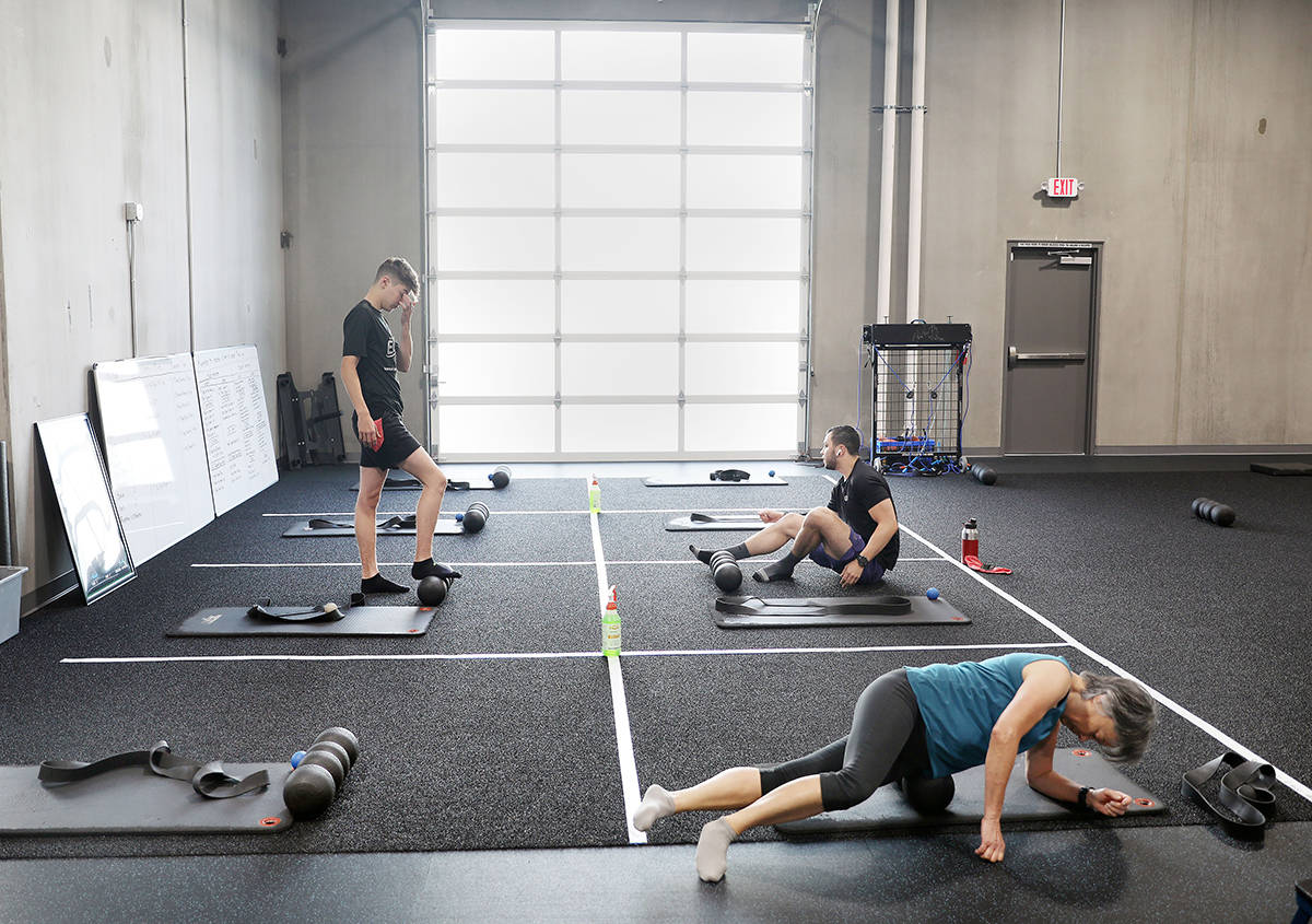 Members of The Gym Las Vegas stretch while following social distancing guidelines the first mor ...