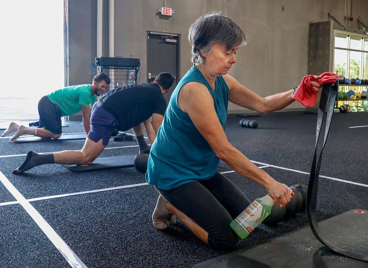 Carole Hedge, 65, member of The Gym Las Vegas, disinfects her mat and band while also following ...