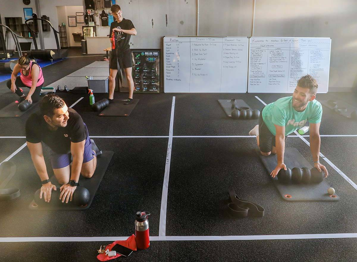 Members of The Gym Las Vegas Brian Lee, left, and Ethan Ryan, 17, stretch while following socia ...