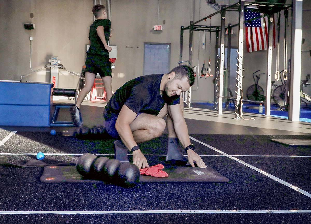 Brian Lee, member of The Gym Las Vegas, disinfects his mat, the first morning on the facility&# ...