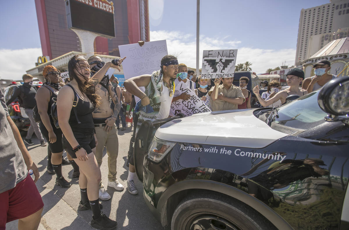 People yell at Las Vegas police in their vehicle during a Black Lives Matter protest and march ...