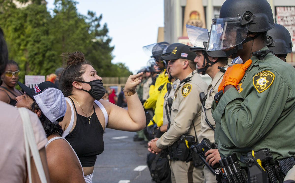 A protestor yells at a Las Vegas Police officer as they are lined up to block progress along th ...