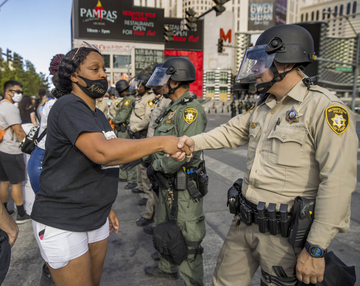 A protestor shakes the hands of each Las Vegas Police officer lined up to block progress down t ...