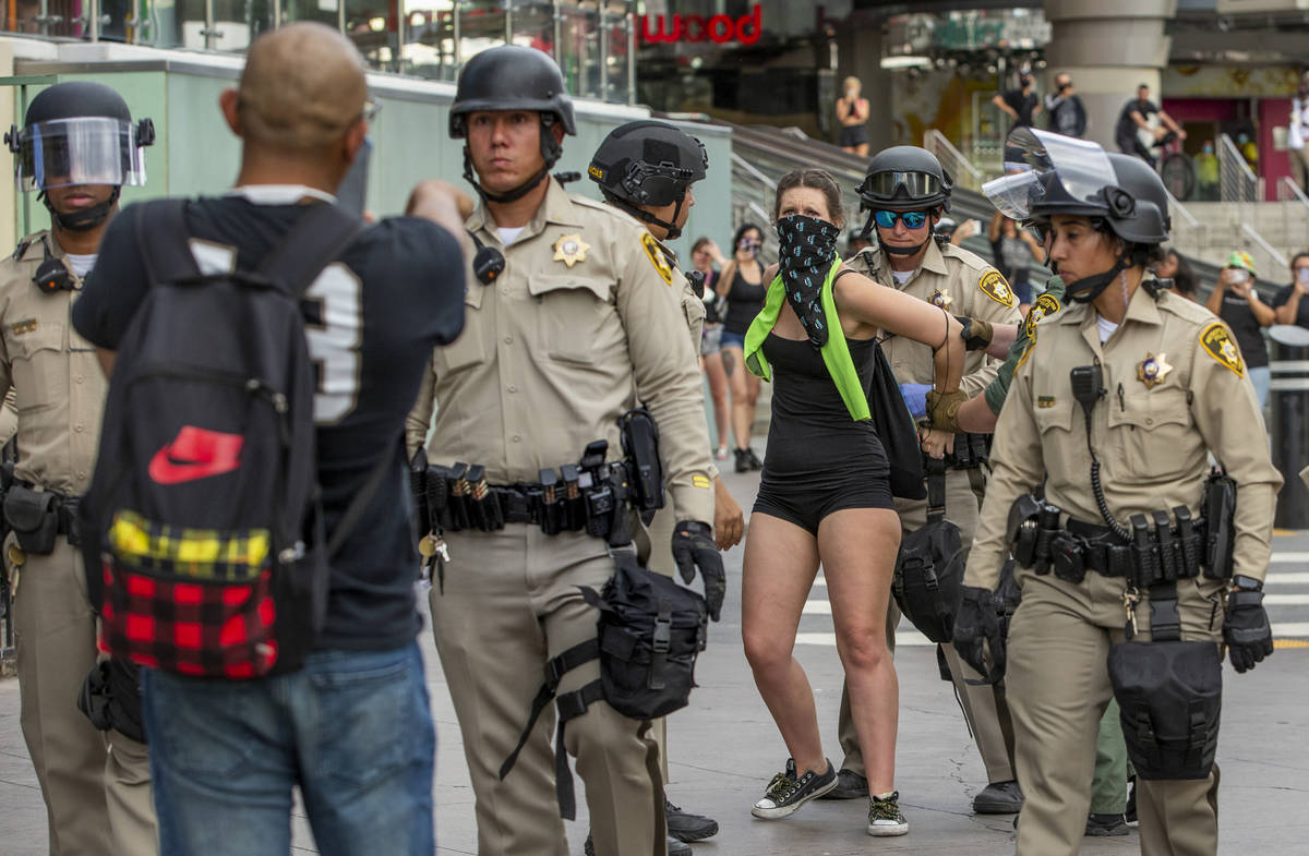 A protestor, right, is arrested as another pleads with Las Vegas Police officers who are lined ...