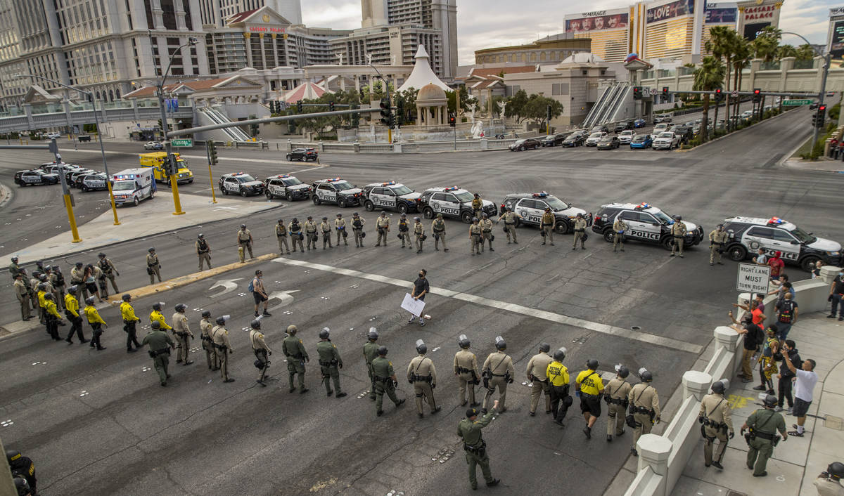 Two protestors are boxed in as Las Vegas Police officers advance up the Las Vegas Strip at W. F ...