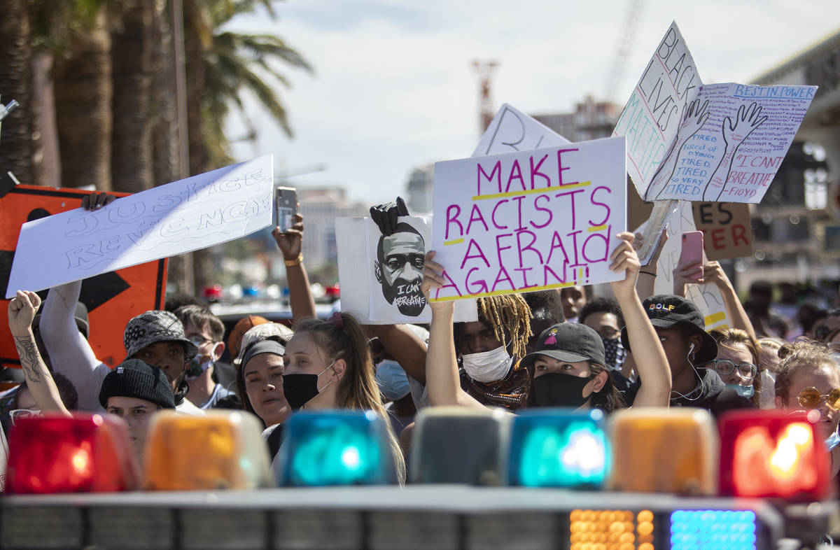 Supporters and members of the Black Lives Matter movement stand before a police vehicle protest ...