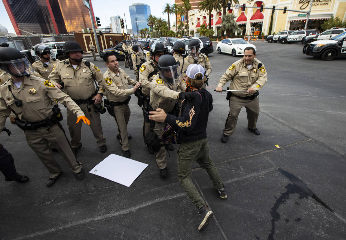 Police arrest a demonstrator as people gather to demand justice for George Floyd along the Las ...