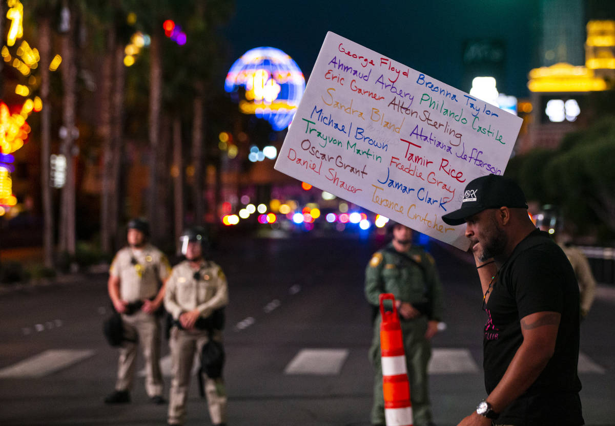 A man holds up a sign with the names of people of color killed by police as a police line block ...