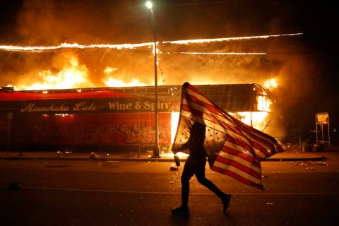A protester carries the carries a U.S. flag upside, a sign of distress, next to a burning build ...
