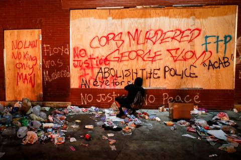 A protestor sprays graffiti on a wall near the Minneapolis 3rd Police Precinct, Thursday, May 2 ...