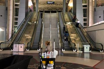 A janitorial employee looks to the few passengers heading through Concourse D in Terminal 3 at ...