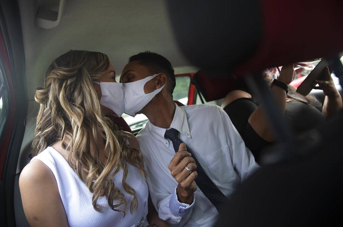 Wearing masks to prevent the spread of the new coronavirus, Thiago do Nascimento, right, and Ke ...