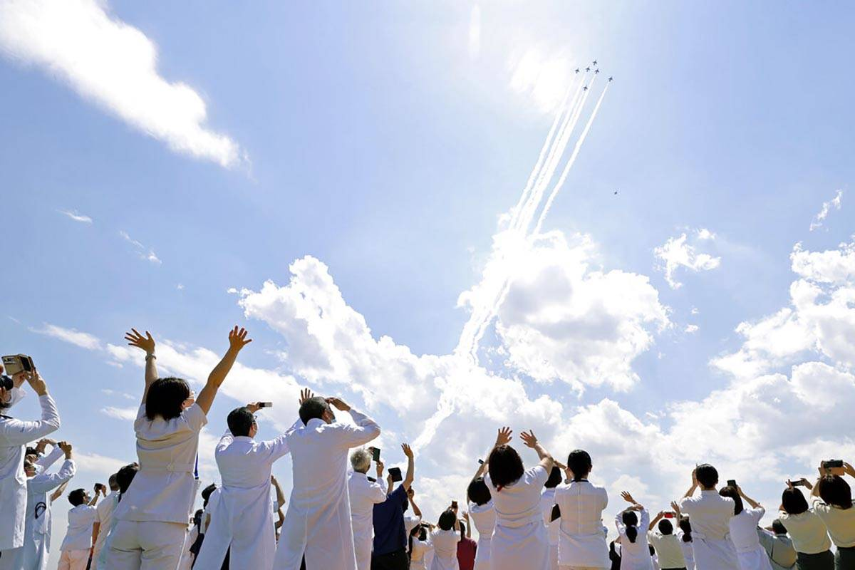 Blue Impulse of the Japan Air Self-Defense Force fly over medical workers of Self-Defense Force ...