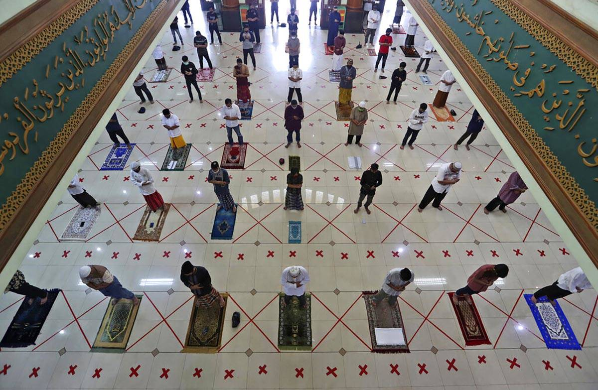 Muslims pray spaced apart to help curb the spread of the coronavirus during a Friday prayer at ...