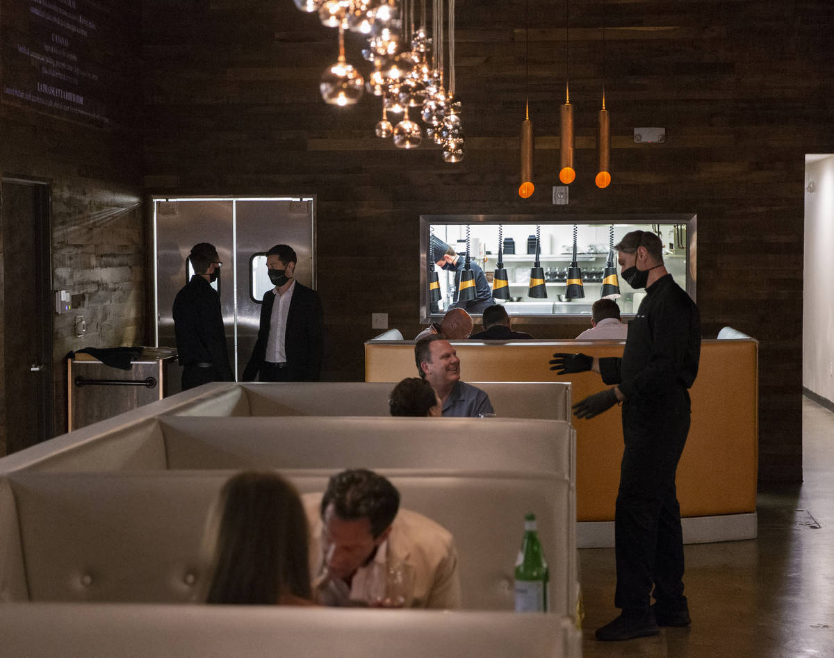 Chef Yuri Szarzewski, top/right, speaks with David and Lisa French during dinner service at Par ...