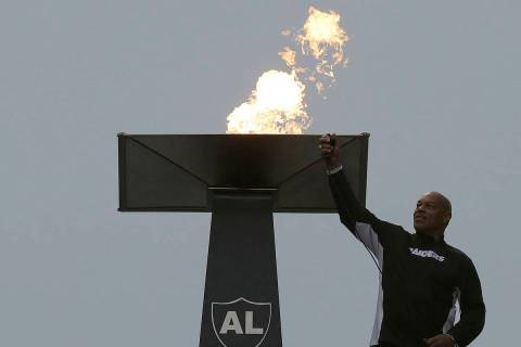 Former NFL football player Greg Townsend lights a ceremonial torch for former Oakland Raiders o ...