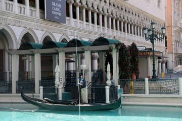 Pool maintenance worker Armando Felix cleans the outdoor canal at The Venetian on the Strip in ...