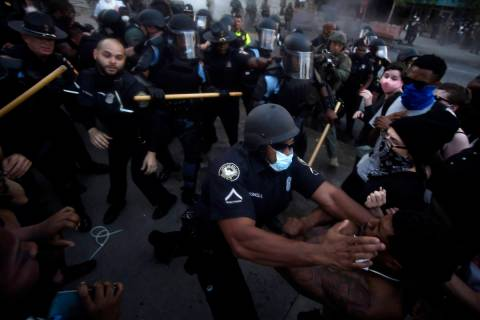 Police officers and protesters clash near CNN Center, Friday, May 29, 2020, in Atlanta, in resp ...