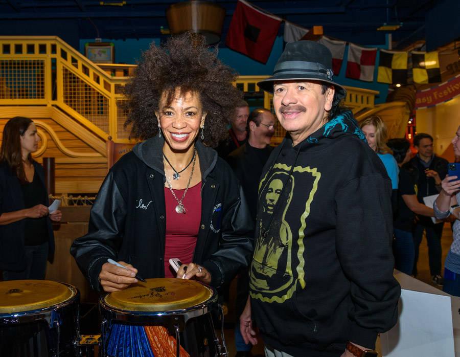 Carlos Santana and Cindy Blackman Santana, shown signing a bongo drum, appear at a Discovery Ch ...