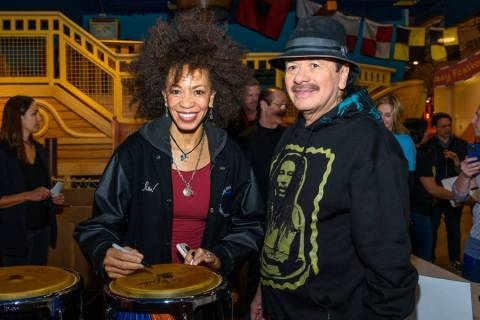 Carlos Santana and Cindy Blackman Santana, shown signing a bongo drum, appear at a Discovery Ch ...