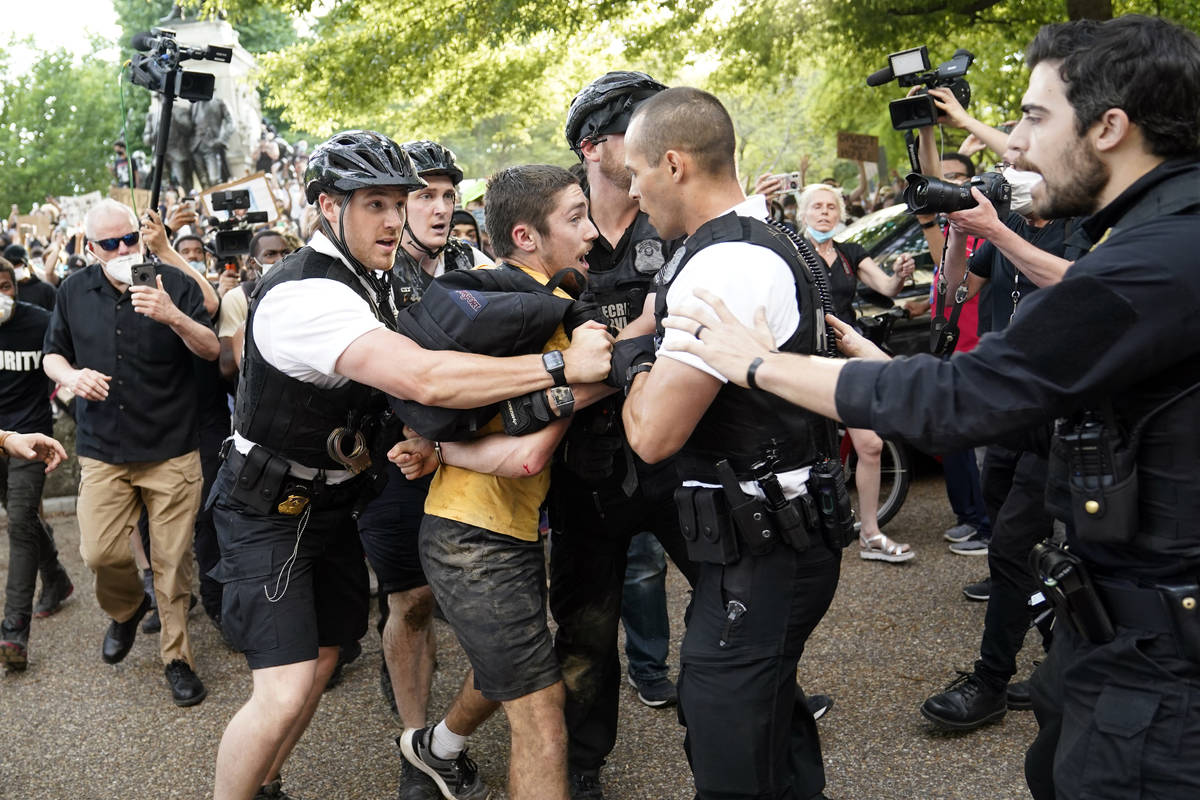 Uniformed U.S. Secret Service police detain a protester in Lafayette Park across from the White ...