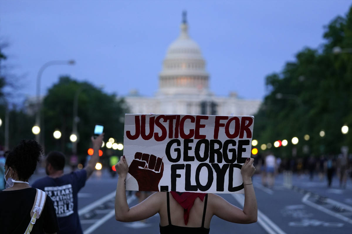 Demonstrators walk along Pennsylvania Avenue as they protest the death of George Floyd, a black ...