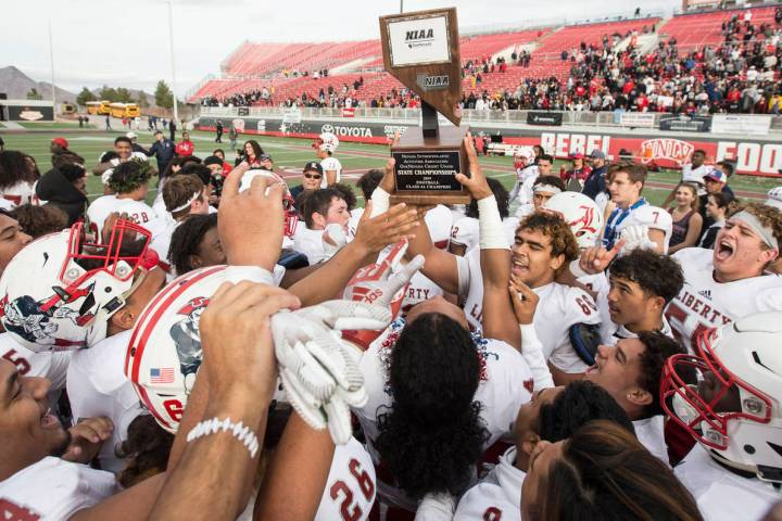 Liberty players celebrate after defeating Centennial 50-7 to win the Class 4A state football ch ...