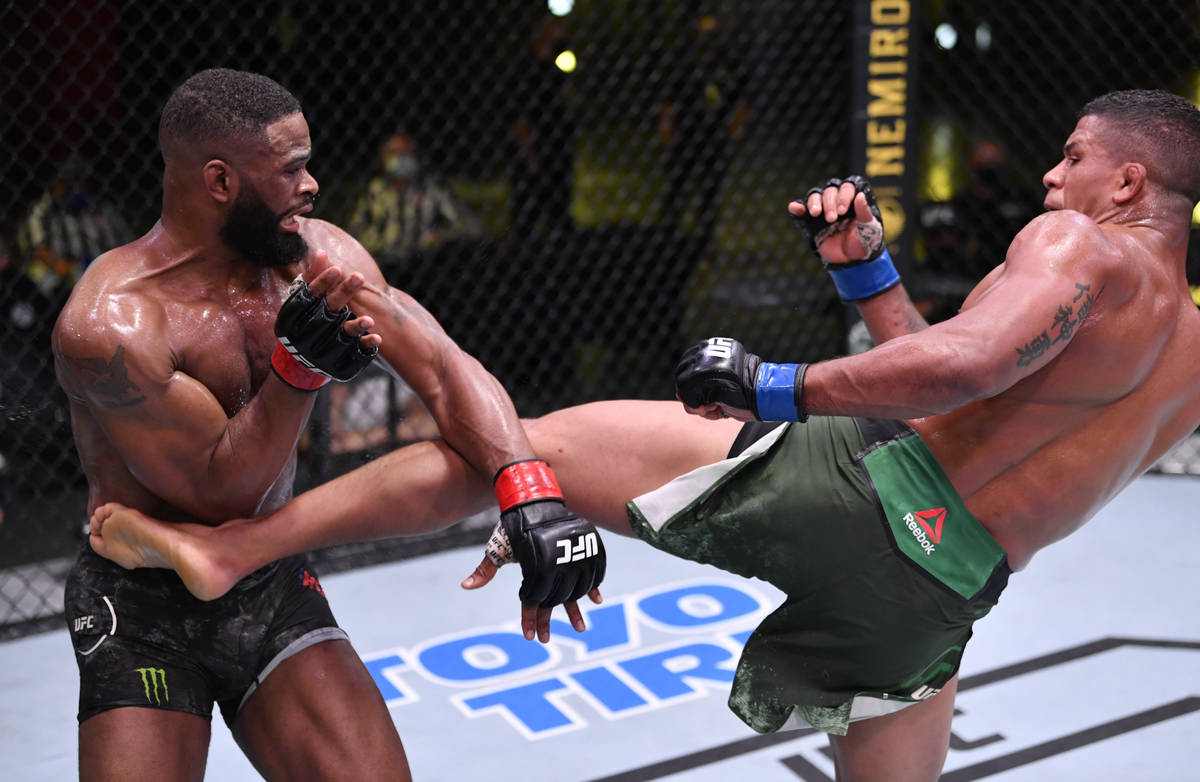 LAS VEGAS, NEVADA - MAY 30: (R-L) Gilbert Burns of Brazil kicks Tyron Woodley in their welterwe ...