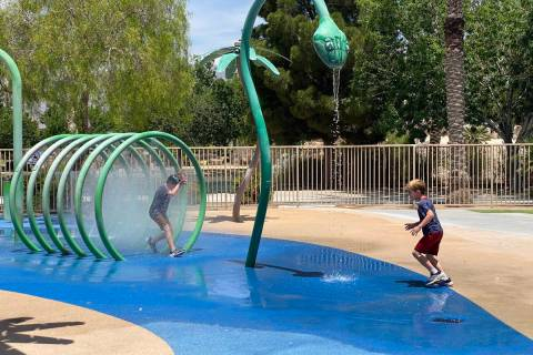 Two children running through sprinklers at Aliante Nature Discovery Park's splash pad as it reo ...