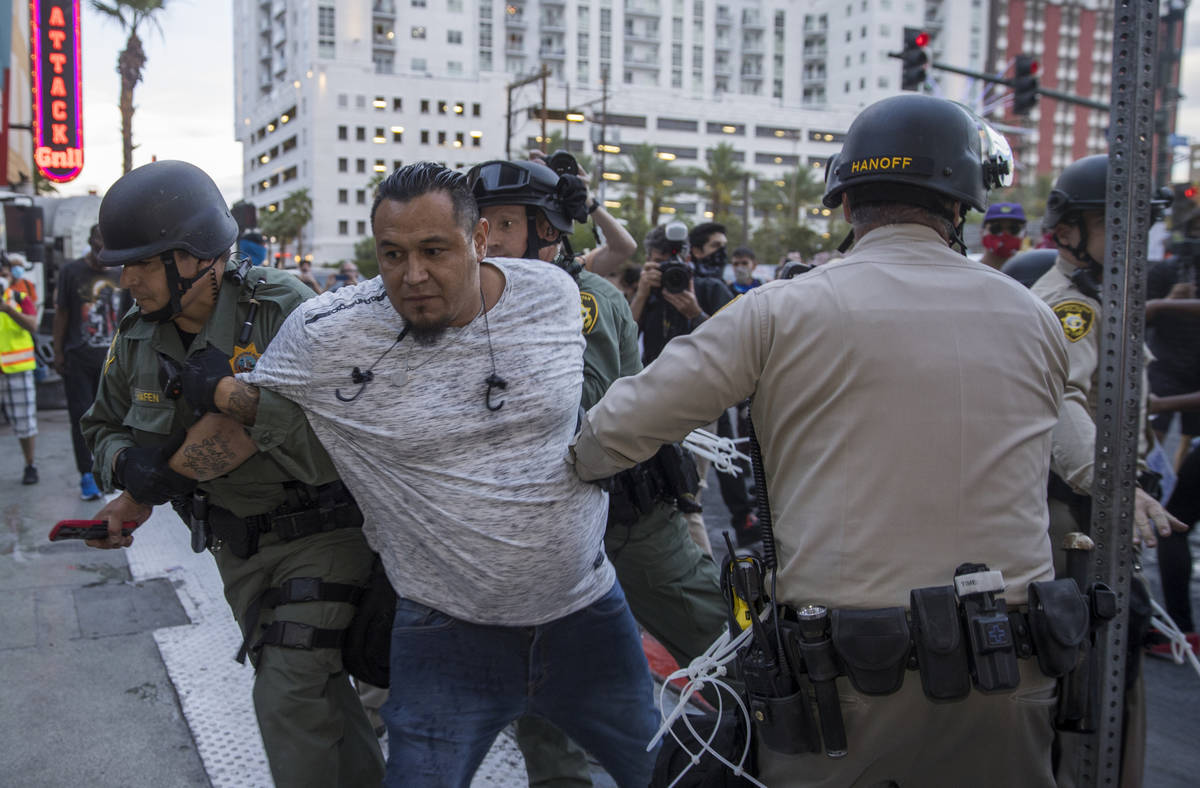 Police arrest a man confronting others at Fremont Street Experience during a Black Lives Matter ...