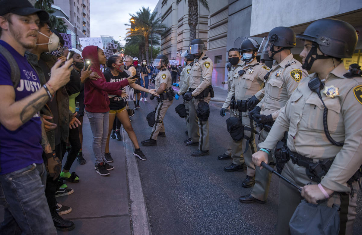 Las Vegas Police look on as protesters confront them while marching along S. Casino Center Driv ...