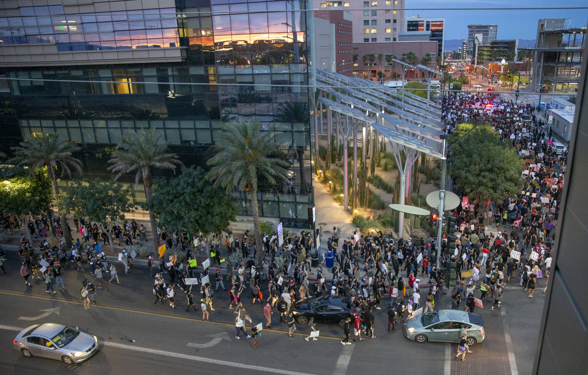 Protesters march past City Hall during a Black Lives Matter protest and march at Container Park ...
