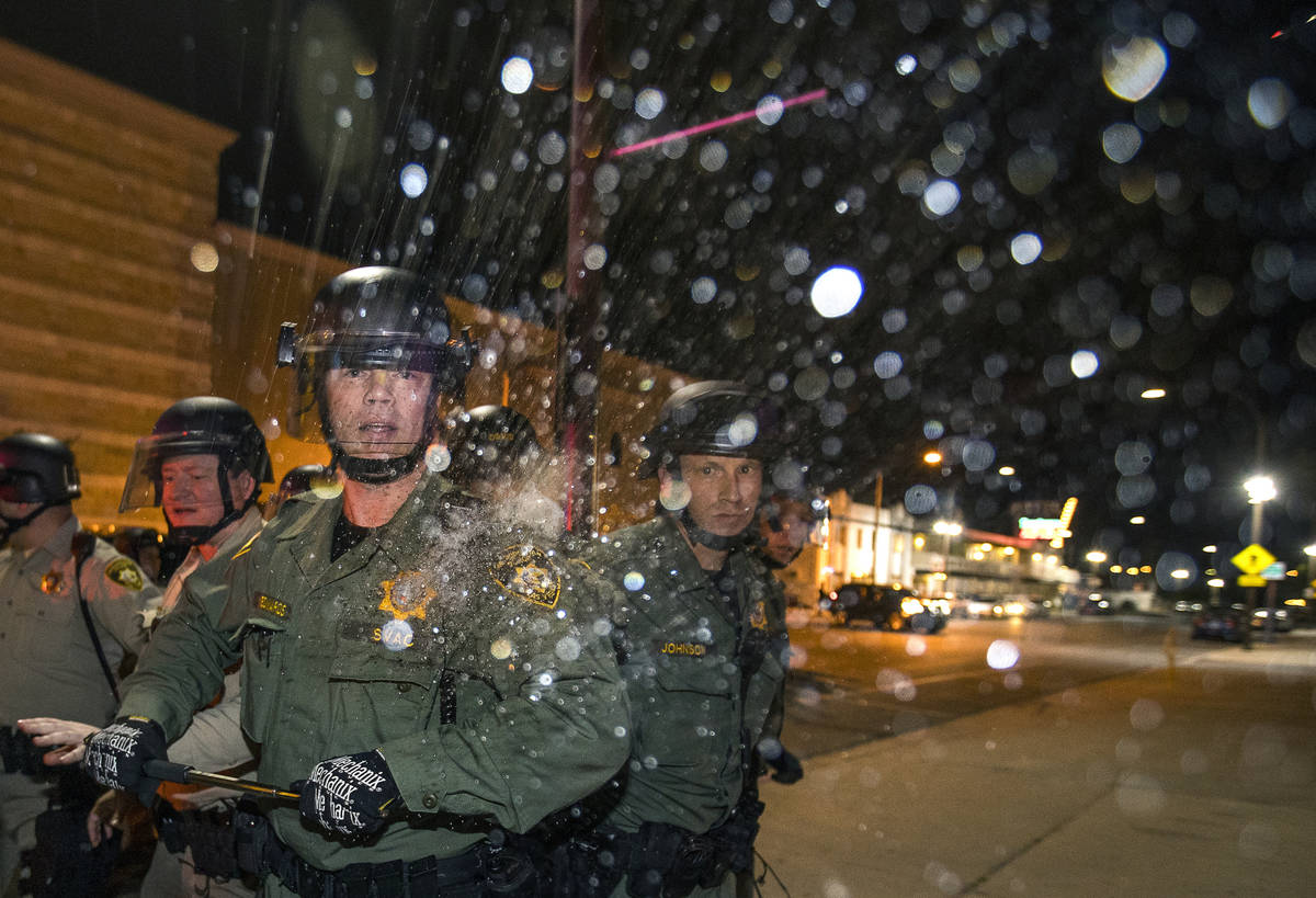 A Las Vegas Police officer is struck on the shoulder by a water bottle during clashes with prot ...