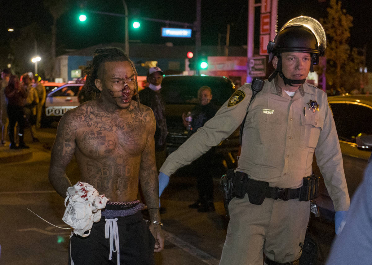 Las Vegas Police officers escort a bloodied protester from a Black Lives Matter march about Con ...