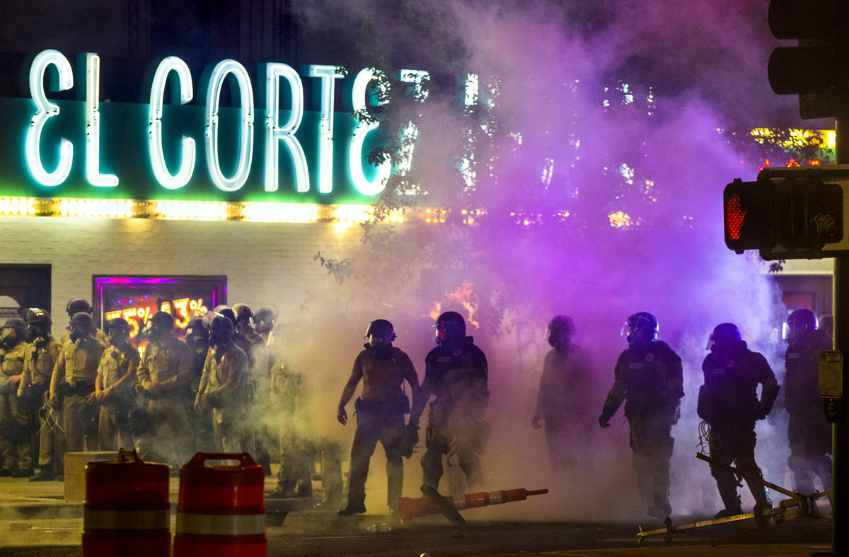Las Vegas Police are engulfed in tear gas as protesters threw the canisters back on Fremont Str ...