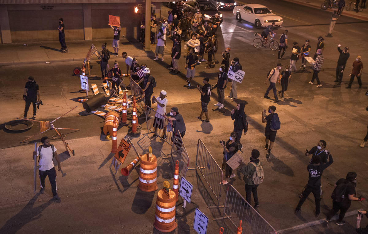 Protesters block the street with signs, barricades and barrels as Las Vegas Police move down La ...