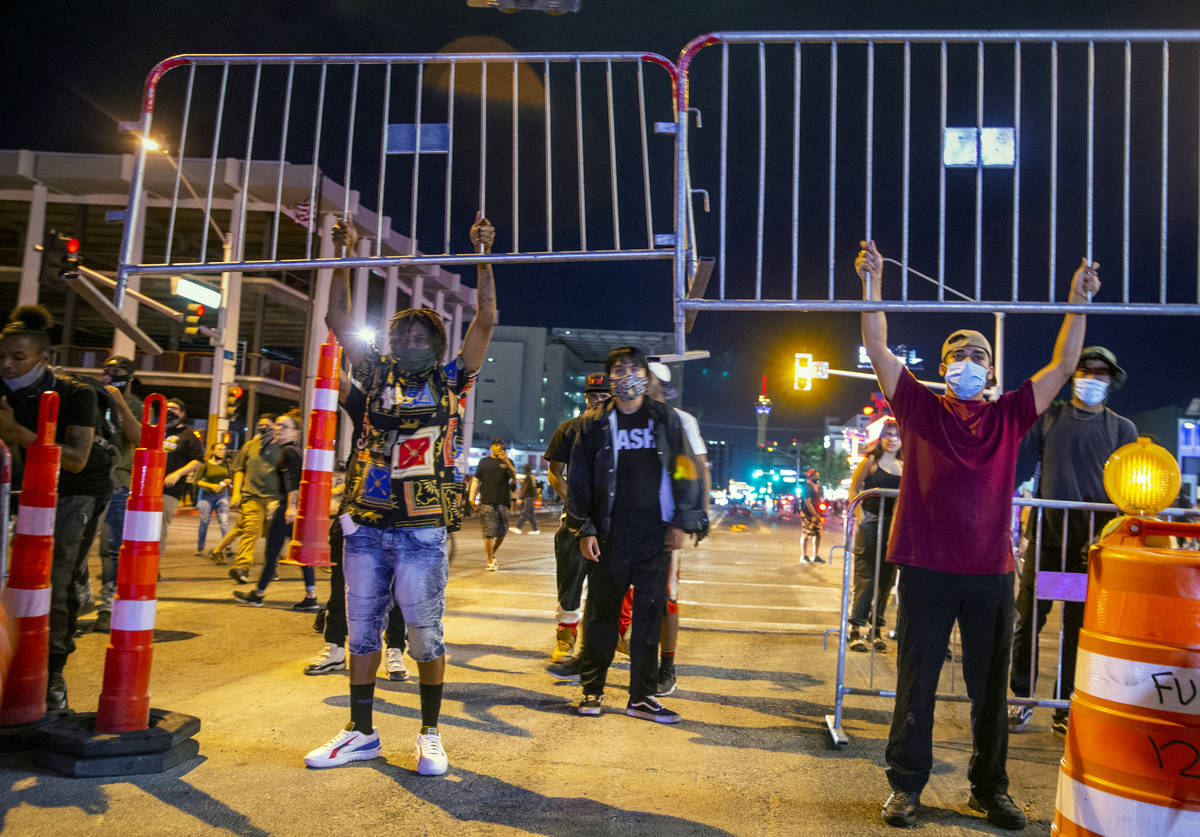 Protesters lift up barricades as they face off with Las Vegas Police on Las Vegas Blvd. as chao ...